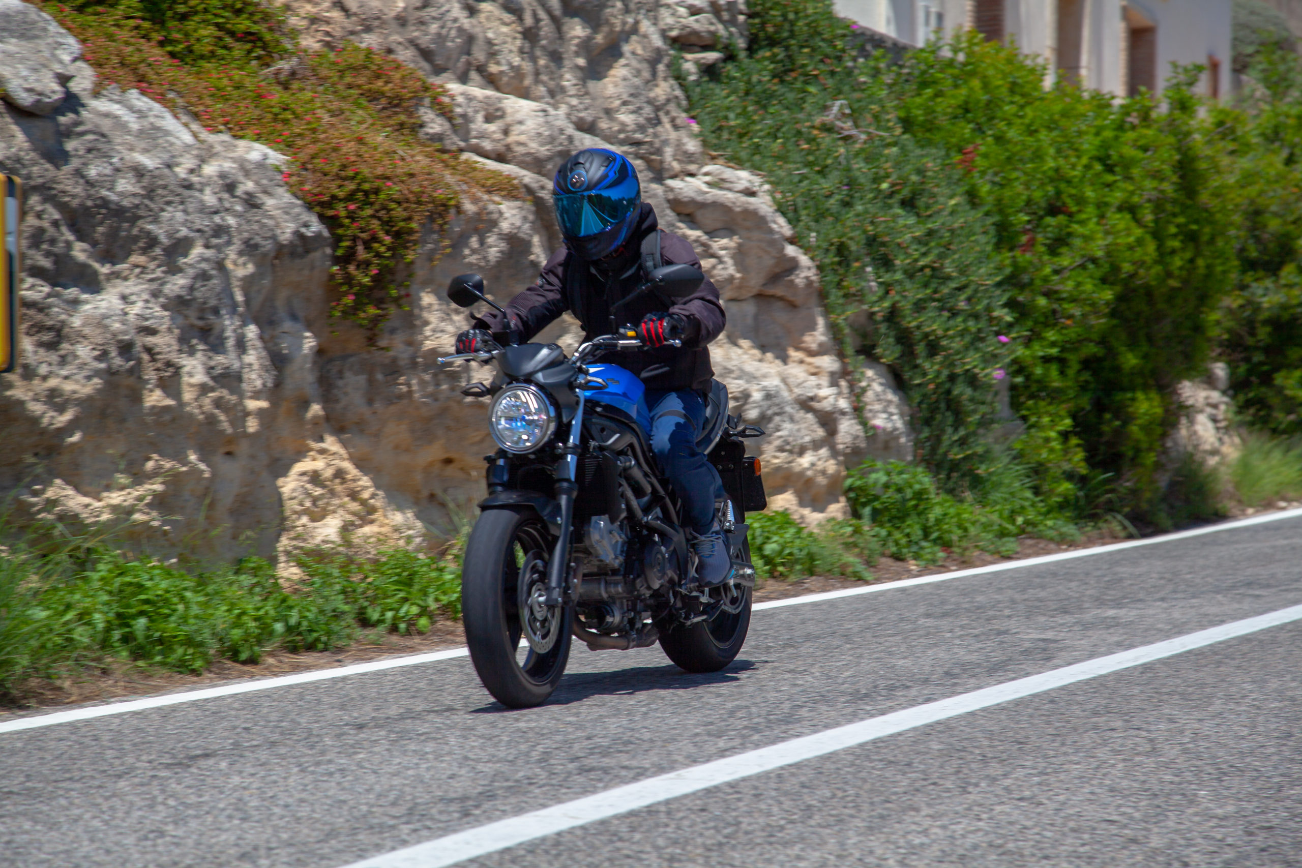 man riding on a blue motorcycle with a blue helmet